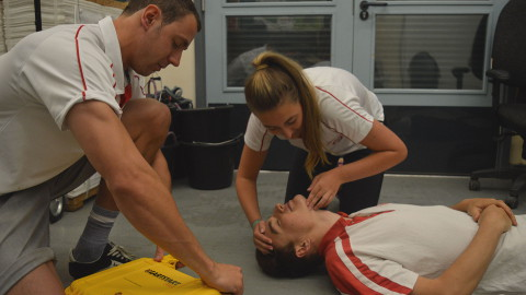 Lifeguards performing first aid training with an AED